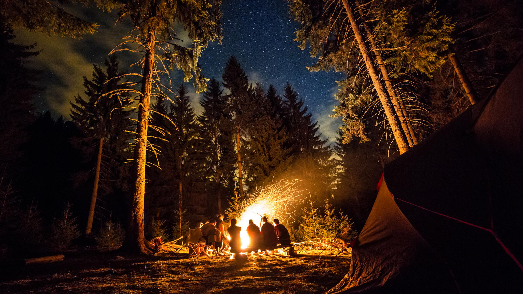 Camping Fire This is an image of a group of people sitting by a camping fire in the mountains. By: TG_Studios
