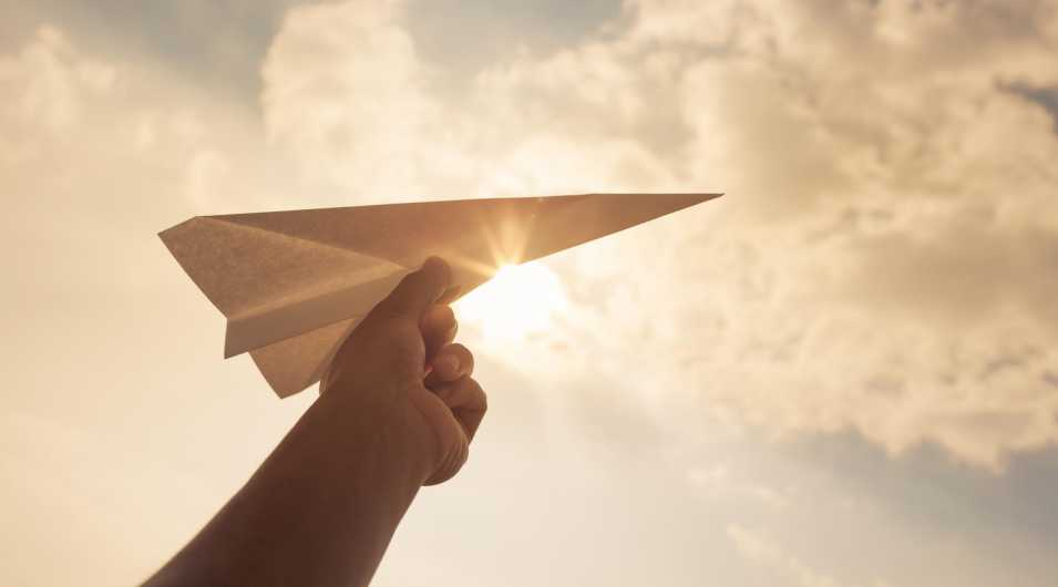 Taking flight! Hand holding paper airplane in the sky. By: This content is subject to copyright.