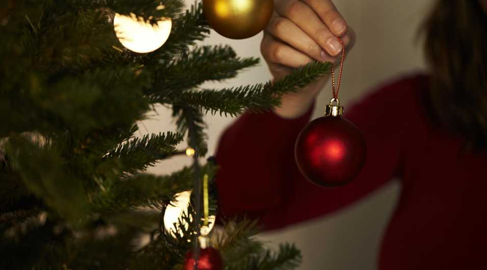 Christmas bauble Woman decorating tree with Christmas bauble, close up By: This content is subject to copyright.